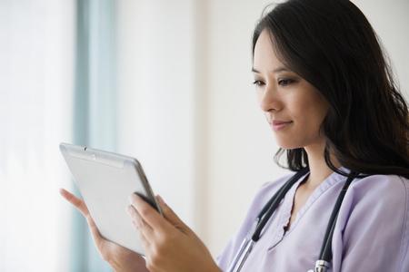 Chinese nurse using digital tablet LANG_EVOIMAGES