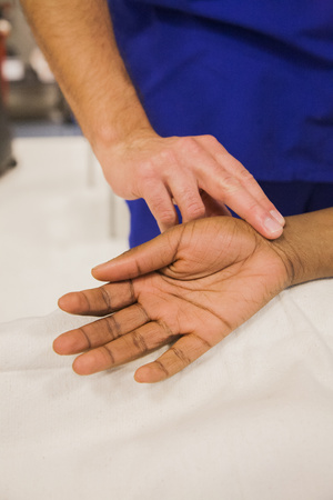 Close up of doctor checking pulse of patient LANG_EVOIMAGES