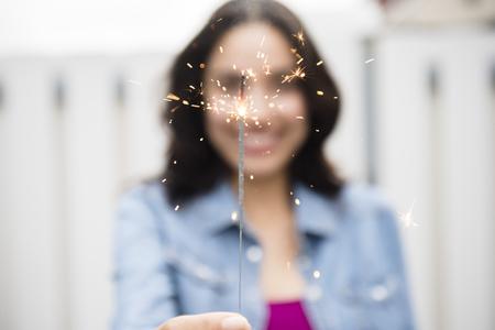 Hispanic woman holding sparkler LANG_EVOIMAGES