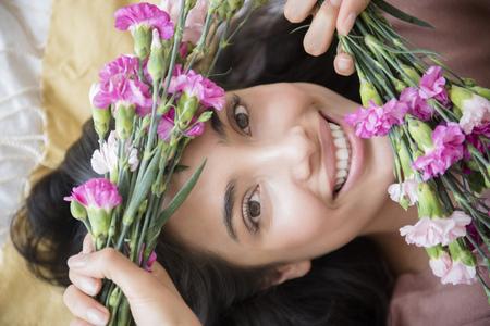 Hispanic woman holding flowers LANG_EVOIMAGES