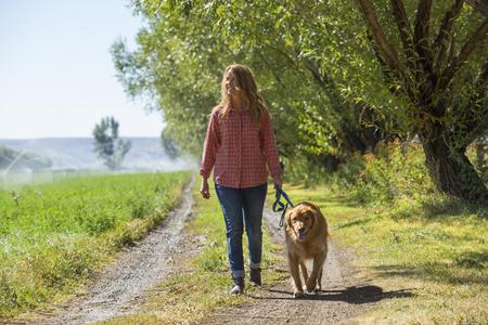 Caucasian woman walking dog on dirt path