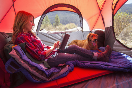 Caucasian woman using digital tablet in camping tent LANG_EVOIMAGES