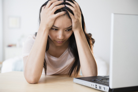 Frustrated Chinese woman using laptop