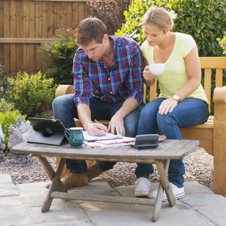 Caucasian couple paying bills in garden