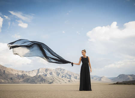 Hispanic woman holding scarf in remote desert LANG_EVOIMAGES