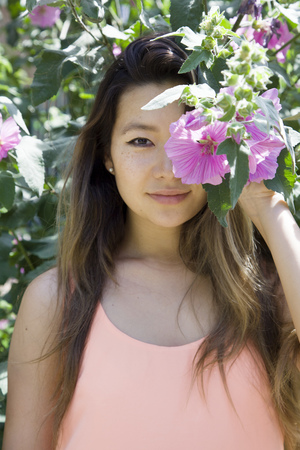 Asian woman hiding behind flower
