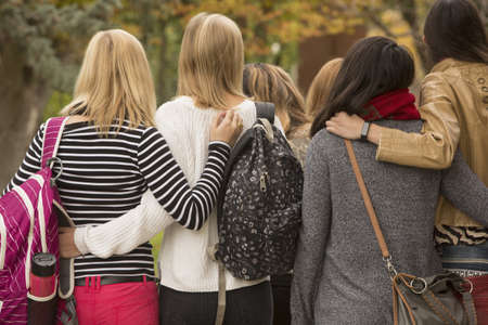 College students hugging on campus LANG_EVOIMAGES