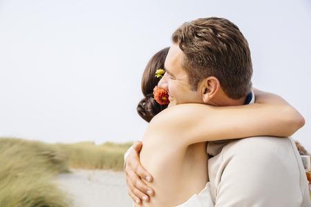 Caucasian bride and groom hugging in outdoor wedding LANG_EVOIMAGES