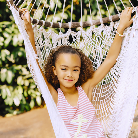 Mixed race girl sitting in hammock LANG_EVOIMAGES