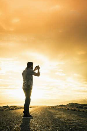 Hispanic man photographing on remote road