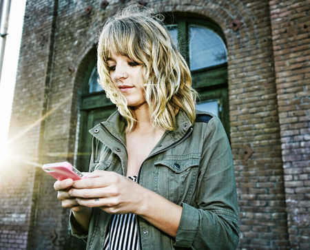 Caucasian woman using cell phone outdoors LANG_EVOIMAGES