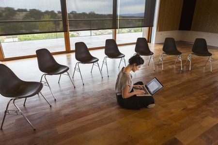 Mixed race businesswoman using laptop on floor of meeting room LANG_EVOIMAGES