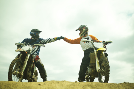 Caucasian men bumping fists on dirt bikes