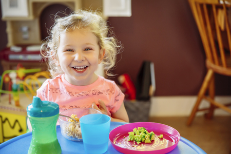 Caucasian girl eating in high chair LANG_EVOIMAGES