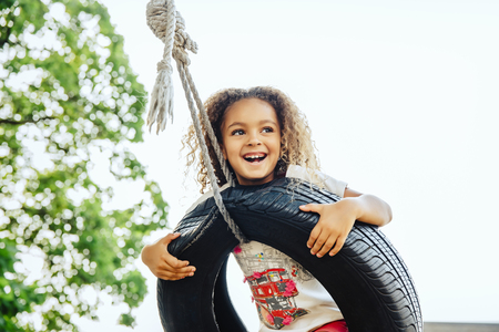 Mixed race girl smiling in tire swing LANG_EVOIMAGES