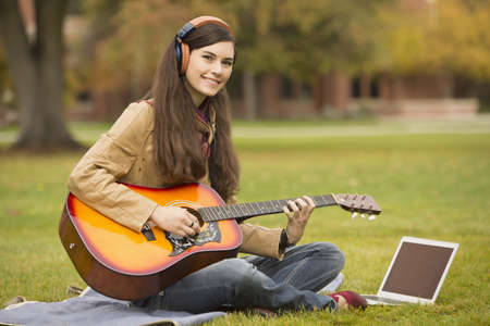 Caucasian college student playing guitar on campus