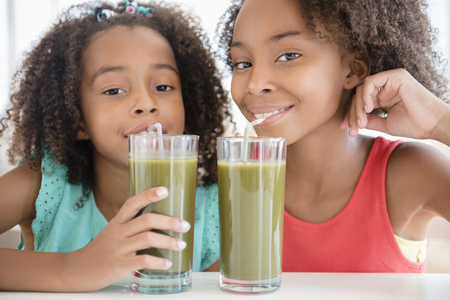 Mixed race sisters drinking healthy juice LANG_EVOIMAGES
