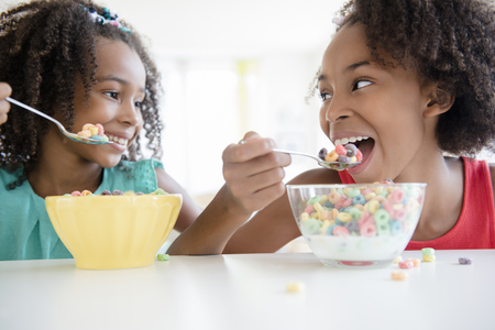 Mixed race sisters eating cereal LANG_EVOIMAGES