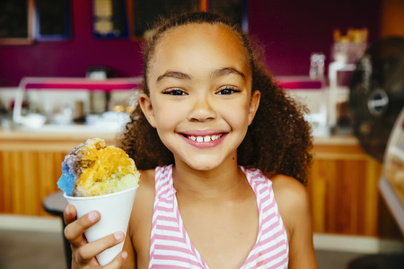 Mixed race girl holding snow cone LANG_EVOIMAGES