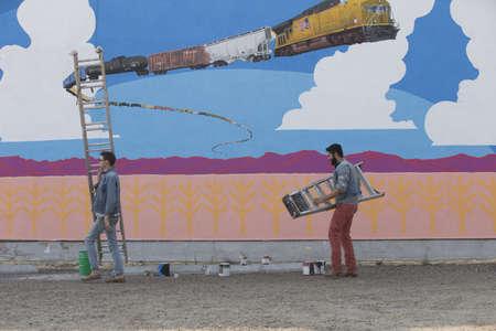 Men carrying ladders at mural wall