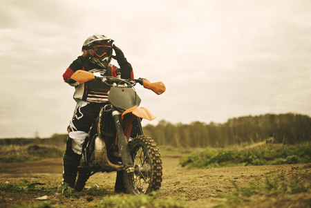 Caucasian man riding dirt bike in field
