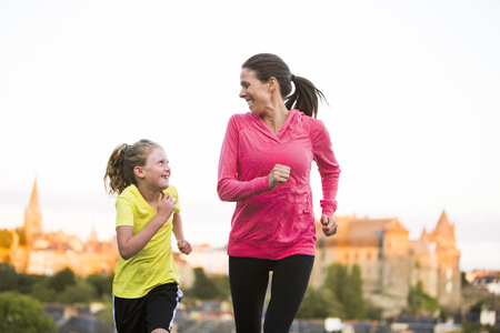 Caucasian mother and daughter jogging outdoors LANG_EVOIMAGES