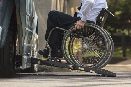 Caucasian businessman in wheelchair entering van