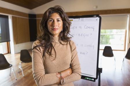 Hispanic businesswoman standing in meeting room LANG_EVOIMAGES