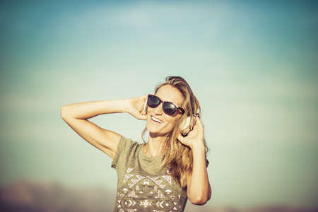 Hispanic woman listening to headphones outdoors