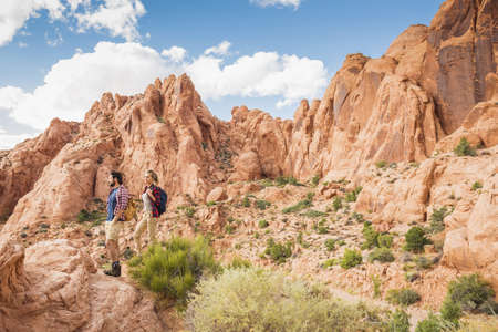 Hispanic couple hiking on remote trail LANG_EVOIMAGES