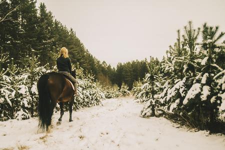 Caucasian woman riding horse on snowy path