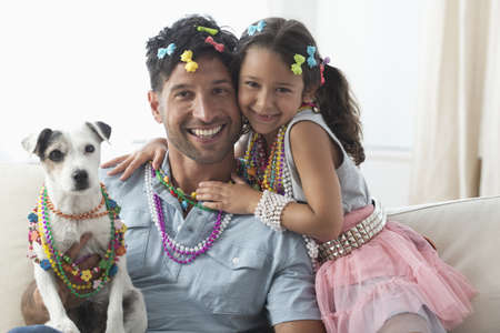 Caucasian father and daughter playing dress-up with dog LANG_EVOIMAGES