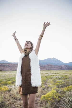 Hispanic woman cheering in rural field