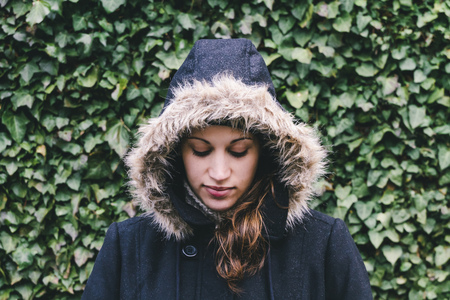 Caucasian woman wearing fur hood
