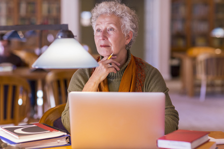 Older mixed race woman using laptop in library LANG_EVOIMAGES