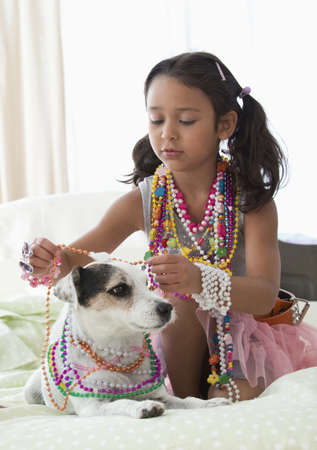 Caucasian girl playing dress-up with dog