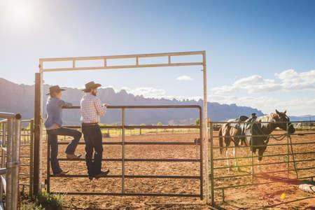 Hispanic ranchers standing on gate