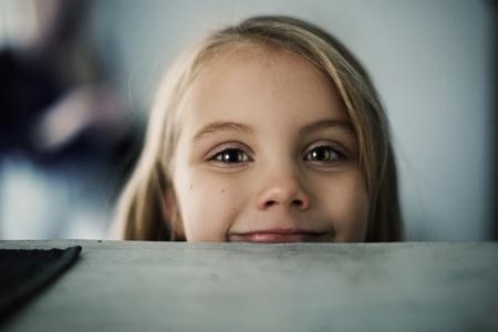 Caucasian girl peering over counter