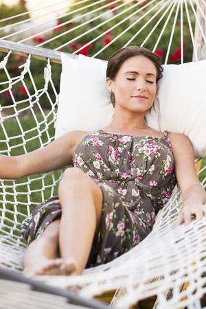 Caucasian woman laying in hammock