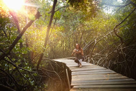 Pacific Islander woman photographing on walkway in jungle