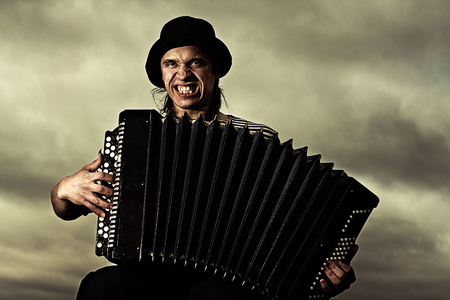 Caucasian man playing accordion outdoors LANG_EVOIMAGES
