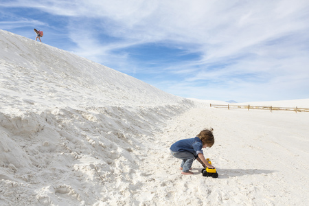 Caucasian boy playing with toy truck in desert LANG_EVOIMAGES