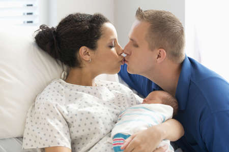 Couple kissing with newborn baby son