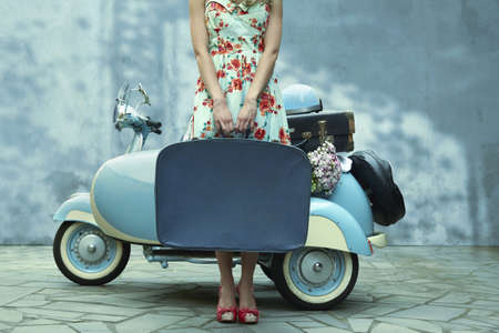 Pacific Islander woman holding suitcase near vintage scooter
