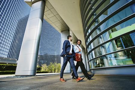 Businessmen walking outside office building