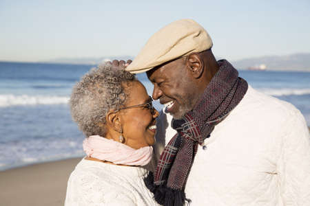 Older African American couple hugging on beach