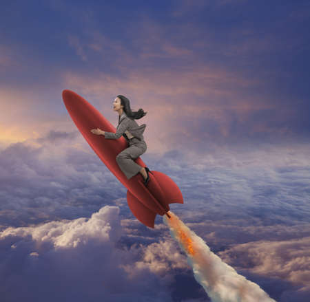 Pacific Islander businesswoman riding rocket in sky