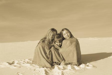 Caucasian children wrapped in blankets in desert LANG_EVOIMAGES