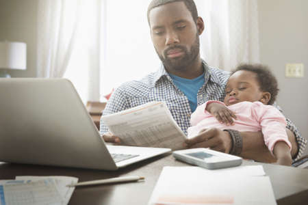 Father holding baby daughter and working from home