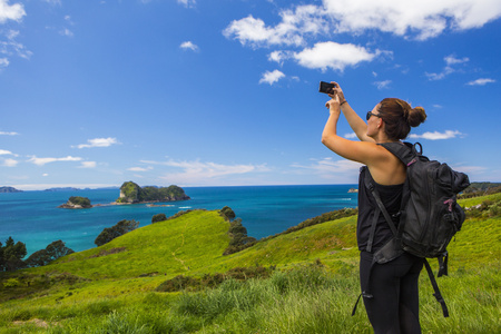 Caucasian hiker photographing cliff and seascape